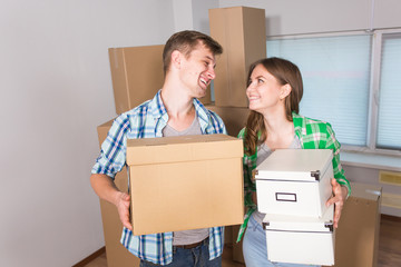 home, people, moving and real estate concept - happy couple with cardboard boxes at new home