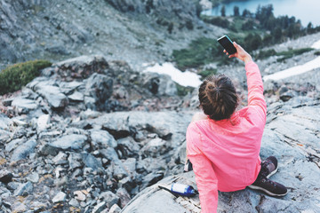 Brave woman sitting high in mountains and taking selfie using her smartphone. Risky rock climbing in peaceful wilderness area. Enjoying amazing snowy lake view