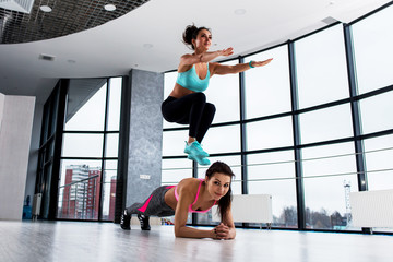 Two sporty Caucasian girls doing partner circuit workout, first woman holding plank position while the partner is squat side jumping over her in sports club