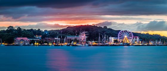 Port city at night with Ferris wheel