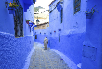 Man in typical moroccan clothing, walking down a street in Chefchaouen city.