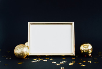 Mock up frame on dark background with Christmas decorations glitter baubles, bell and stars confetti. Invitation, card, paper. Place for text Trendy black and gold