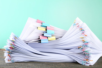 Stack of papers with paperclips and clamps on wooden table