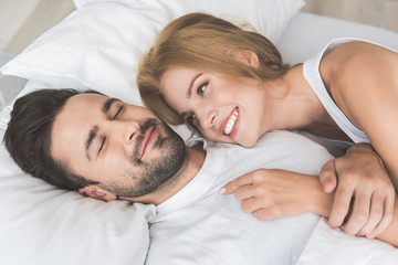 Cheerful loving couple relaxing in bedroom