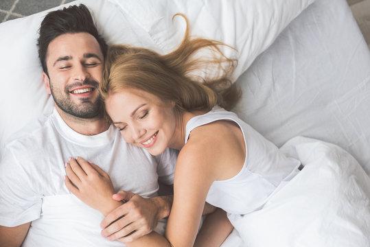 Joyful loving couple luxuriating in bedroom together