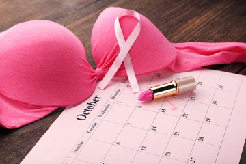 Pink ribbon on female bra with pomade and calendar sheet