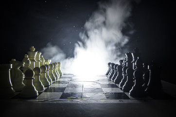 Chess board game concept of business ideas and competition and strategy ideas concep. Chess figures on a dark background with smoke and fog