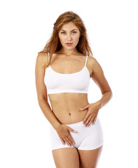 Young beautiful blonde woman in white fitness clothing