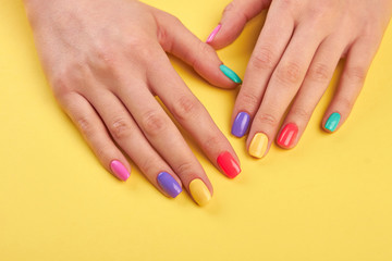 Aluminium Prints Manicure Female well-groomed hands with manicure. Young girl hands polished with different colors nail on yellow wooden background.