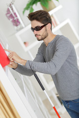 blind young man with stick and dark glasses at home