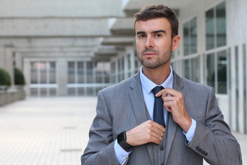 Boastful businessman adjusting his tie