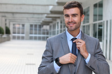 Elegant businessman adjusting his tie with copy space