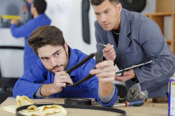 car mechanic replacing timing belt of modern engine