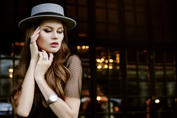 Outdoor portrait of young beautiful fashionable woman posing in street. Model wearing stylish gray hat, net t-shirt, wrist watch, a lot of rings. Female fashion. Copy, empty space for text