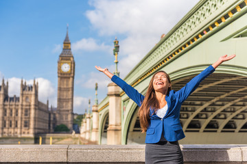 Wall Mural - London success happy businesswoman winning with open arms up screaming of joy in happiness. Asian woman cheering at Big Ben Tower, Westminster, London, UK.