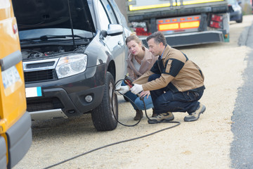 male mechanic inflating a car tire near his female client