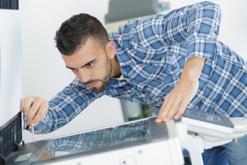man leaning over open photocopier during maintenance repairs using screwdriver