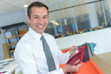 smiling businessman choosing color samples in office
