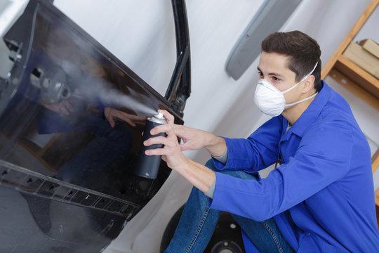 coachbuilder painting a car door