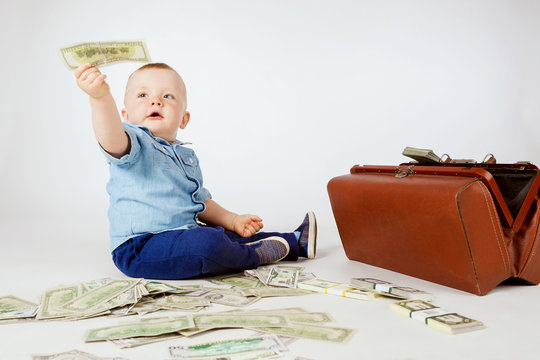The little boy is holding out the money. A baby child holds dollars in his hand. A boy with money.