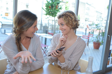 woman showing her mobile phone to a friend in restaurant