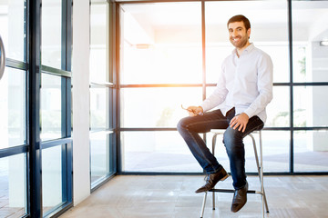 Young business man sitting on a stool in office