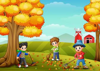 Children raking leaves in the farm yard during fall season