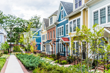 Fototapeta Row of colorful, red, yellow, blue, white, green painted residential townhouses, homes, houses with brick patio gardens in summer obraz