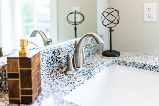 Closeup of modern bathroom sink with granite countertop, mirror, soap dispenser pump and faucet in staging model home, apartment or house