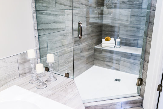 Closeup of staging modern stone grey tiled bathroom, marble countertop in model home, apartment or house with candles, towels, pouf, soap dispenser, glass shower door