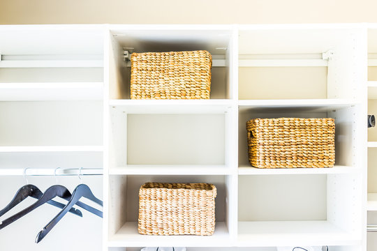 Closeup of woven straw baskets in modern minimalist white closet or laundry room with bright light in staging model house or apartment with hangers