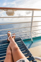Cruise ship travel woman relaxing sun tanning onboard on deck balcony lying down on lounger chair with feet and legs up.