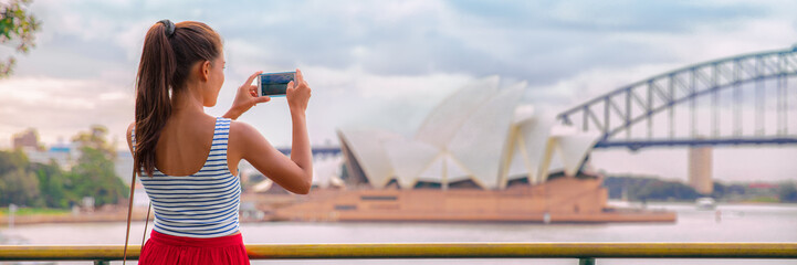 Australia Sydney travel tourist woman at Opera House panoramic banner landscape crop. Asian girl taking photos with mobile phone during summer vacation trip.