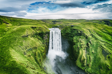 Poster Cascades Iceland waterfall Skogafoss in Icelandic nature landscape. Famous tourist attractions and landmarks destination in Icelandic nature landscape on South Iceland. Aerial drone view of top waterfall.