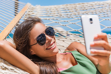 Wall Mural - Vacation woman using smart phone taking smartphone selfie. Girl relaxing on beach hammock sun tanning in sunglasses smiling using cellphone to take pictures and text sms messages.