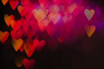 Abstract background of colorful hearts on black backdrop. Bokeh of defocused glitters, blurred yellow and pink symbols of love. Festive wallpaper of holidays and celebrations, St. Valentine's day