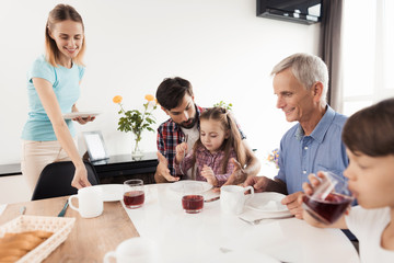 The woman arranges the plates before her family, who is waiting for dinner and is already sitting at the table