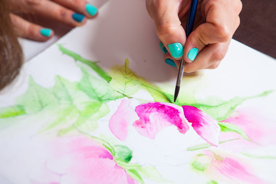 Close-up of the artist draws watercolor in the album for drawing with a thin wooden brush, on the table a pallet for drawing and a mug with tools
