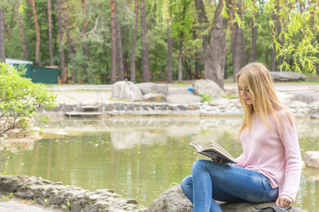 Cute romantic blond teenage-girl is reading a book sitting under the tree in the city park in the sunny weather. A pond surrounded by rocks with trees reflexion in the water is at the background.
