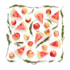 A composition of fruits in a square format on a white background. Pattern made from fresh fruits: apples, grapes, watermelon slices and juniper branches. Top view, flat design. Christmas decor.
