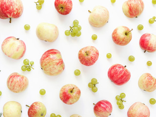 A composition of fruits  on a white background. Pattern made from fresh fruits: apples and grapes. Top view, flat design.