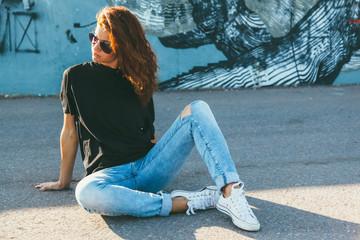 Model wearing plain tshirt and sunglasses posing over street wall Wall mural