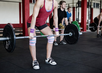 Low Section Of Female Trainer Lifting Barbell