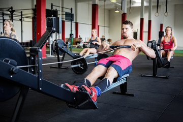 Muscular Man Using Rowing Machine In Gymnasium
