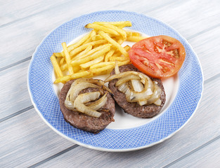 Hamburger with fries, onion and tomato on blue plate next to napkin on wooden table. Food.