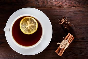 White porcelain cup of tea with cinnamon sticks, lemon, mint leaves and tea strainer