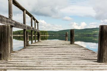Little wooden pier on mountain lake in Dalarna region, Sweden.