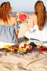 Two young female friends  on the sea shore enjoying  with watermelon.