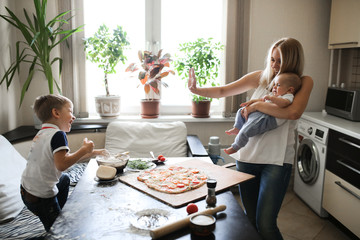 caucasian mum with baby and brother throw in flour