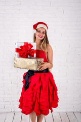 lovely woman in red dress with heap of xmas presents. shoot of studio